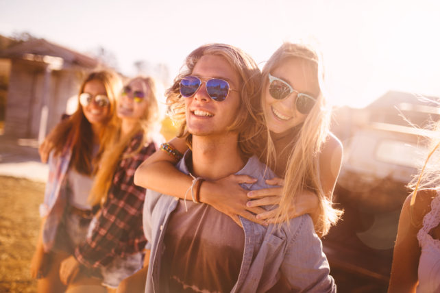 Handsome teen guy wearing sunglasses piggybacking his girlfriend outdoors with friends on a summer day